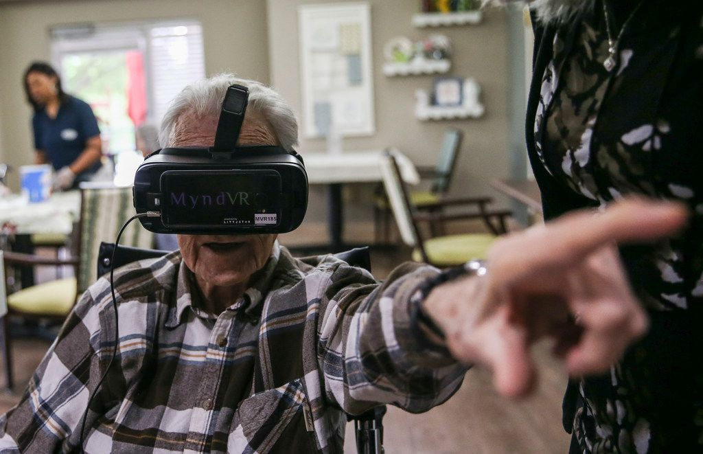 Patrick May, a resident at Signature Pointe assisted living, points as he experiences virtual reality through a headset.