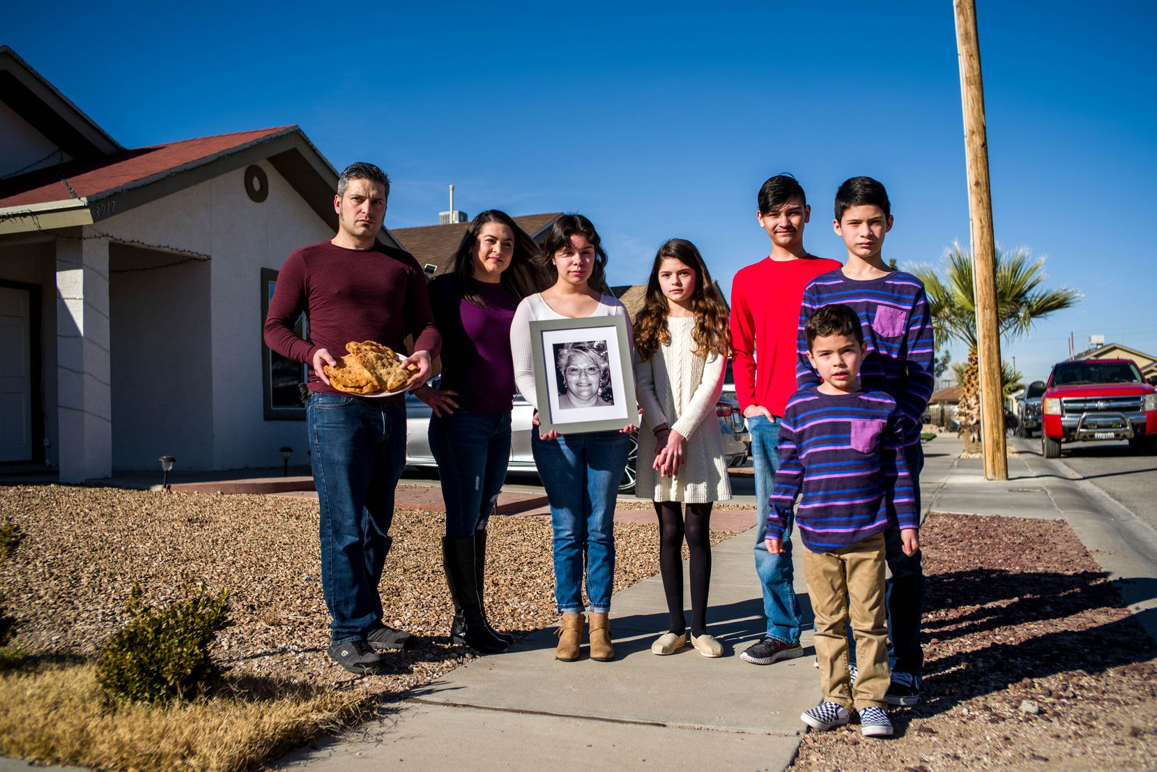 Armando Martínez, left, 35, his wife Muriel Martínez, 33, niece Jasmine Martínez, 19, daughter Maya Martínez, 12, nephew Diego Martínez, 13, son Christopher Martínez, 13, and son Sebastian Martínez, 5, pose for a portrait outside their home as they gather around a photograph of Maria Oralia Lugo, 56, in El Paso, Texas, on Thursday, December, 17, 2020. Maria Oralia Lugo and two other relatives died of COVID-19 in November.