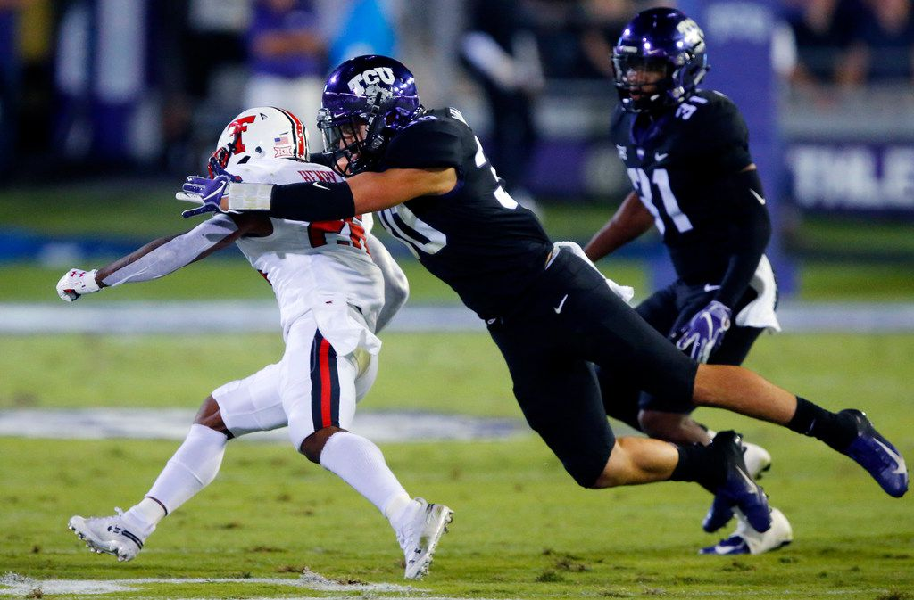 FILE - TCU linebacker Garret Wallow (30) tackles Texas Tech running back Ta'Zhawn Henry (26) during the first half of a game at Amon G. Carter Stadium in Fort Worth on Thursday, Oct. 11, 2018.