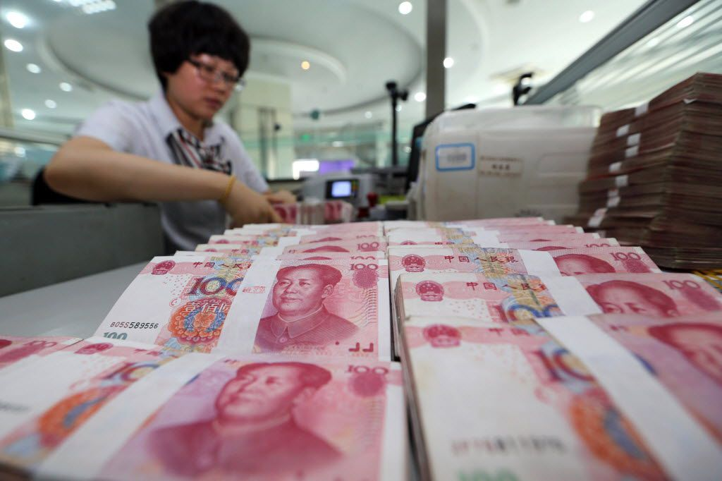 A teller counts yuan banknotes in a bank in Lianyungang, east China's Jiangsu province on August 11, 2015.