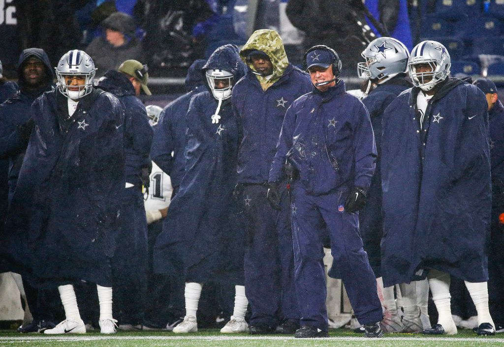 Dallas Cowboys head coach Jason Garrett, third from right, looks to the field during the second half of an NFL matchup between the New England Patriots and the Dallas Cowboys at Gillette Stadium in Foxborough, Massachusetts on Sunday, Nov. 24, 2019.