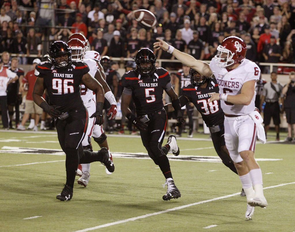 Oklahoma's quarterback Baker Mayfield passes under heavy pursuit by Tech. Texas Tech in an NCAA college football game Saturday, Oct. 22, 2016,  in Lubbock, Texas. (Mark Rogers/Lubbock Avalanche-Journal via AP)