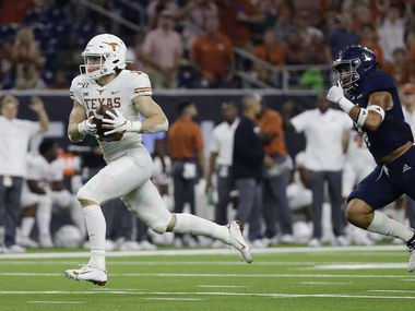 FILE - Texas wide receiver Jake Smith races to the end zone after making a catch past Rice defensive back Prudy Calderon (4) in the first half of a game on Saturday, Sept. 14, 2019, in Houston. (AP Photo/Eric Gay)