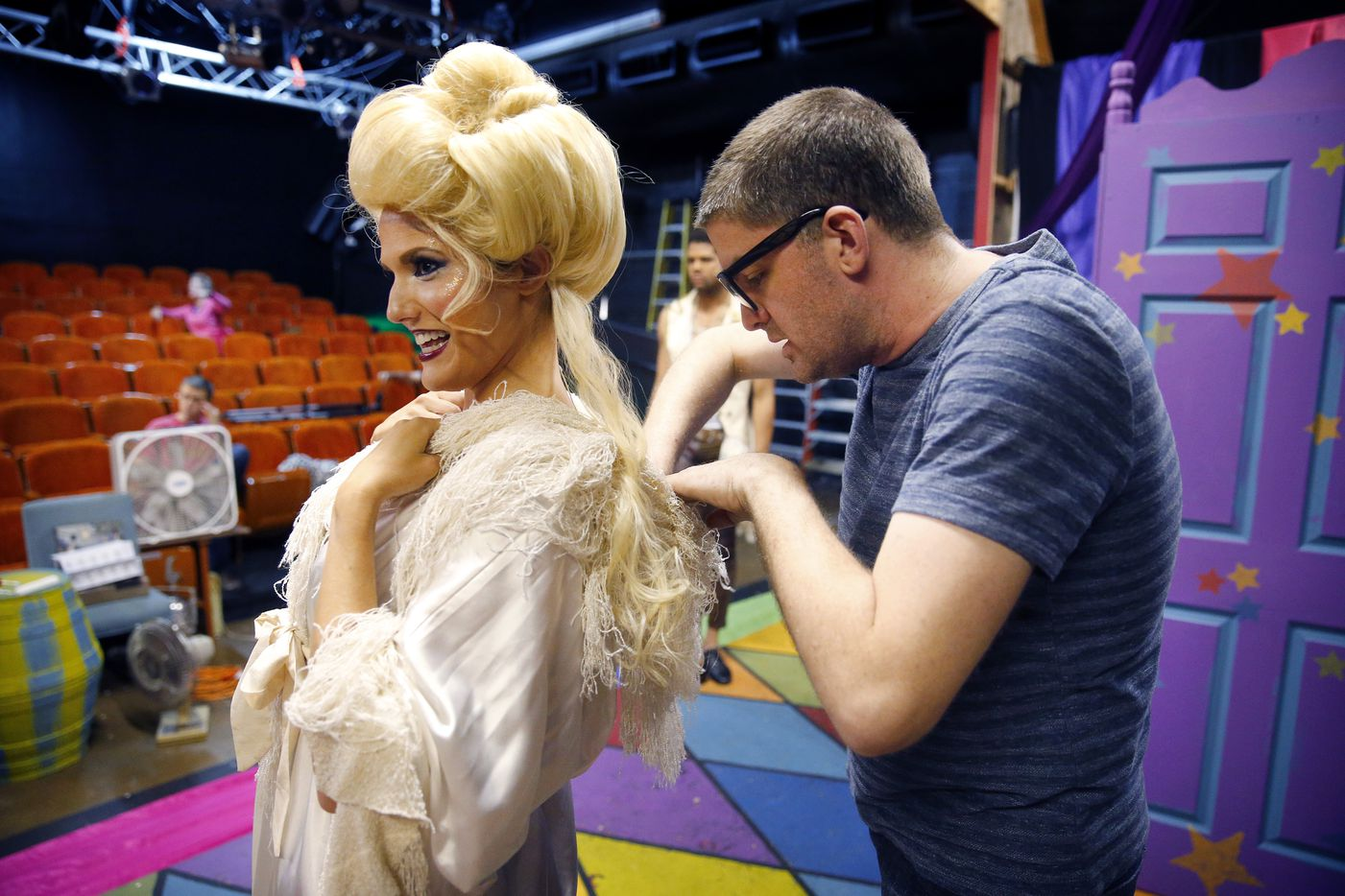 Director Derek Whitener (right) tries to make a fitting adjustment for Kim Borge Swarner (Fastrada) before a dress rehearsal.