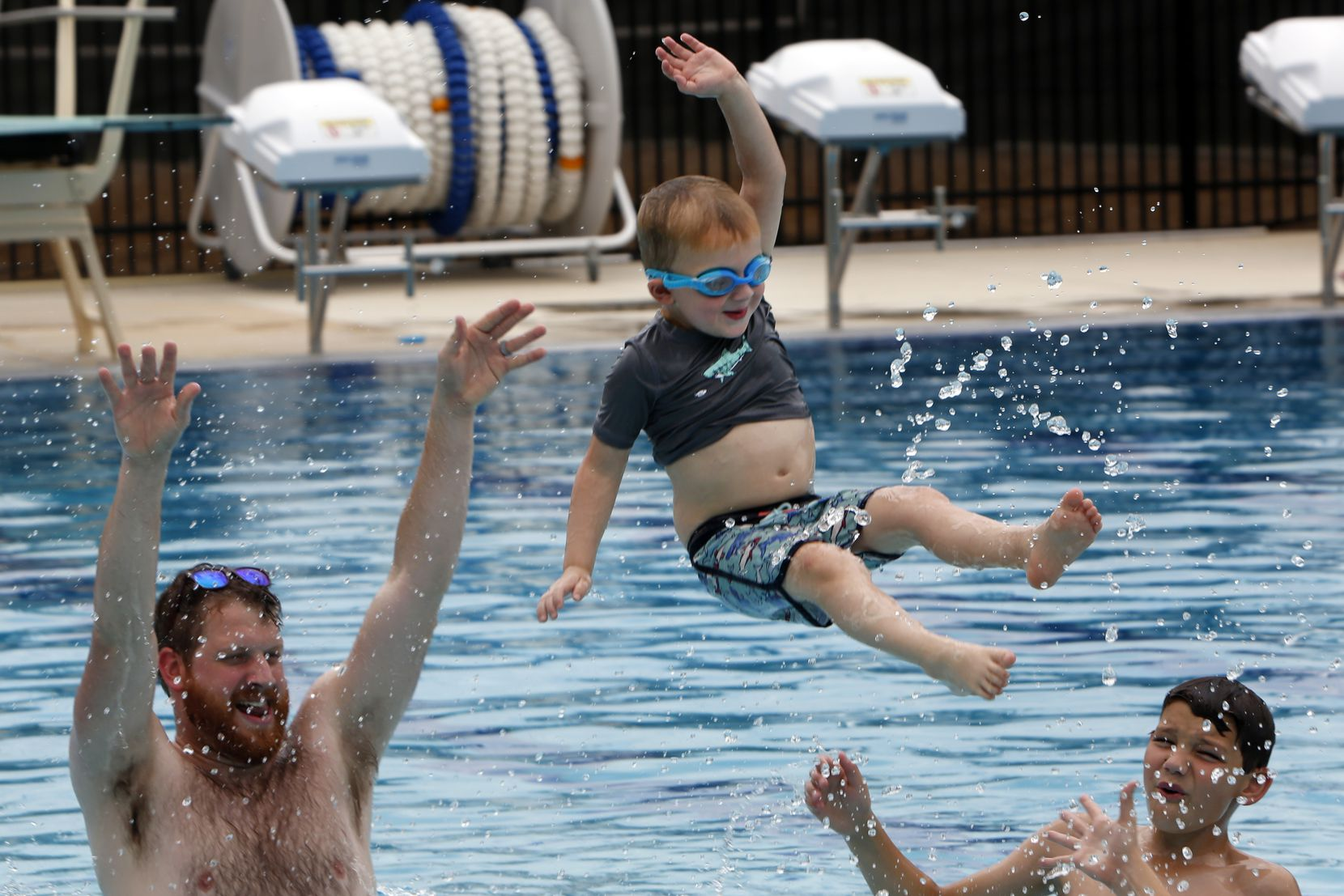 Zeke Koelpin, 3, mimics the form of a bull rider as he flies through the air after being launched by dad Micah as Elijah,11, looks on.