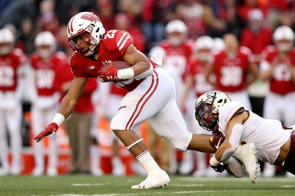 MADISON, WISCONSIN - NOVEMBER 24:  Jonathan Taylor #23 of the Wisconsin Badgers runs with the ball while being tackled by Jacob Huff #2 of the Minnesota Golden Gophers in the first quarter at Camp Randall Stadium on November 24, 2018 in Madison, Wisconsin. (Photo by Dylan Buell/Getty Images)