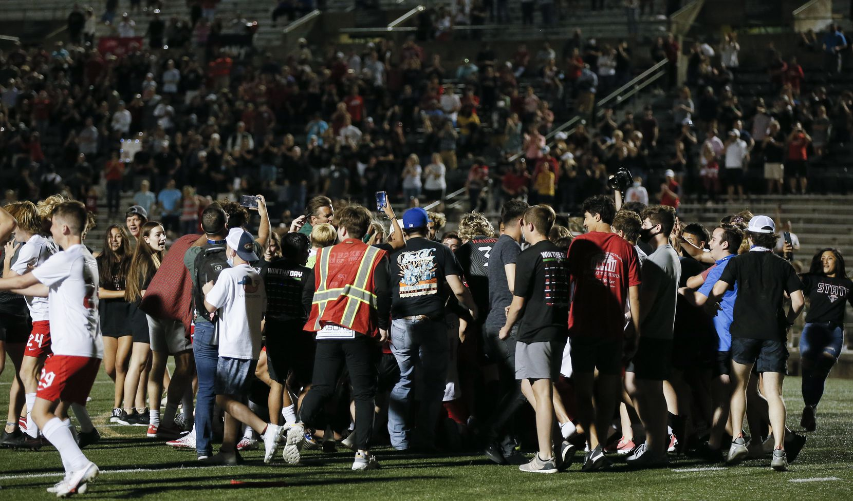 Fans rush the field to celebrate with the Rockwall-Heath boys soccer team after winning the Class 6A state semifinal over Allen 3-1 in a shootout at Mesquite Memorial Stadium in Mesquite, Tuesday, April 13, 2021. (Brandon Wade/Special Contributor)