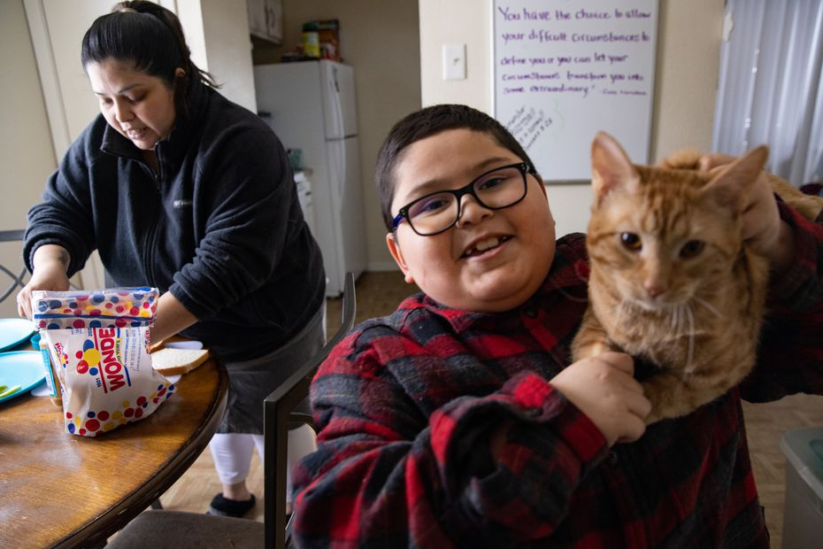 David Sanroman, 7, shows his cat Luna as mother Rosa Mendoza prepares him a PB&J sandwich during a power outage at their Piedmont Addition apartment in Dallas on Wednesday, Feb. 17, 2021. Mendoza's pipes burst Tuesday and hasn't had consistent power. (Juan Figueroa/ The Dallas Morning News)