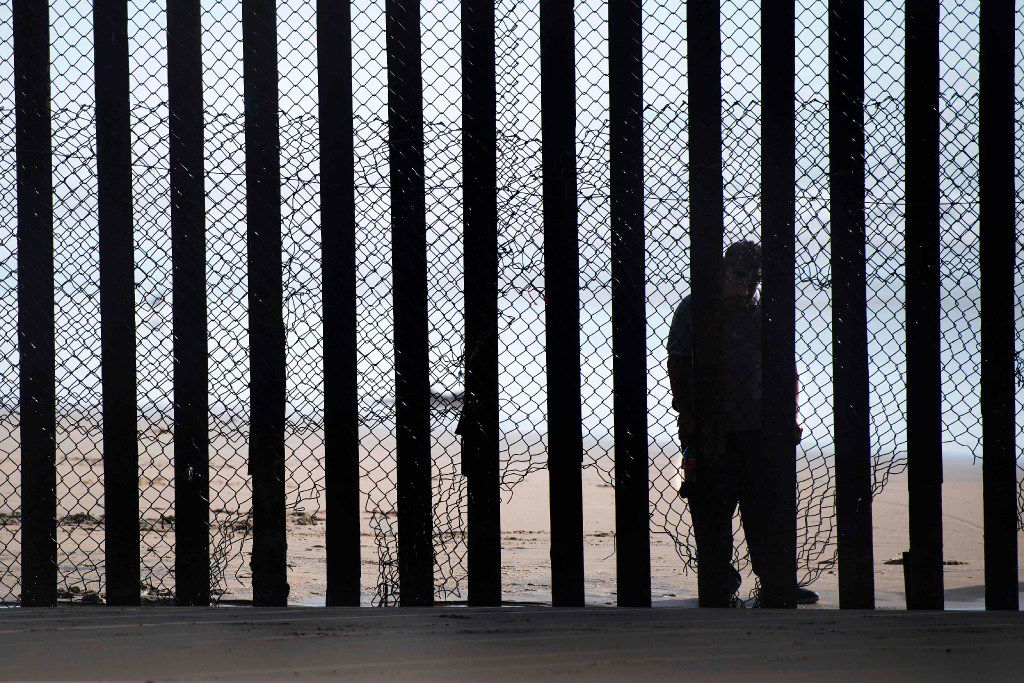 """This file photo taken on February 13, 2017 shows  a man standing on the Mexico side of a border fence separating the beaches at Border Field State Park, in San Diego, CA.  Some Hispanic business owners in the United States are offering to help build President Donald Trump's wall to keep out unauthorized immigrants on the Mexican border, despite controversy and their personal misgivings.""""Myself, being an Hispanic makes it tougher,"""" Michael Luera, who runs a construction services firm in Ganado, Texas, told AFP.His company, Fairfield Logistics, recently expressed interest in working on the border wall project, which has become a lightning rod for public outrage in the debate over Trump's immigration policies. But it was not an easy choice. JIM WATSON/AFP/Getty Images"""