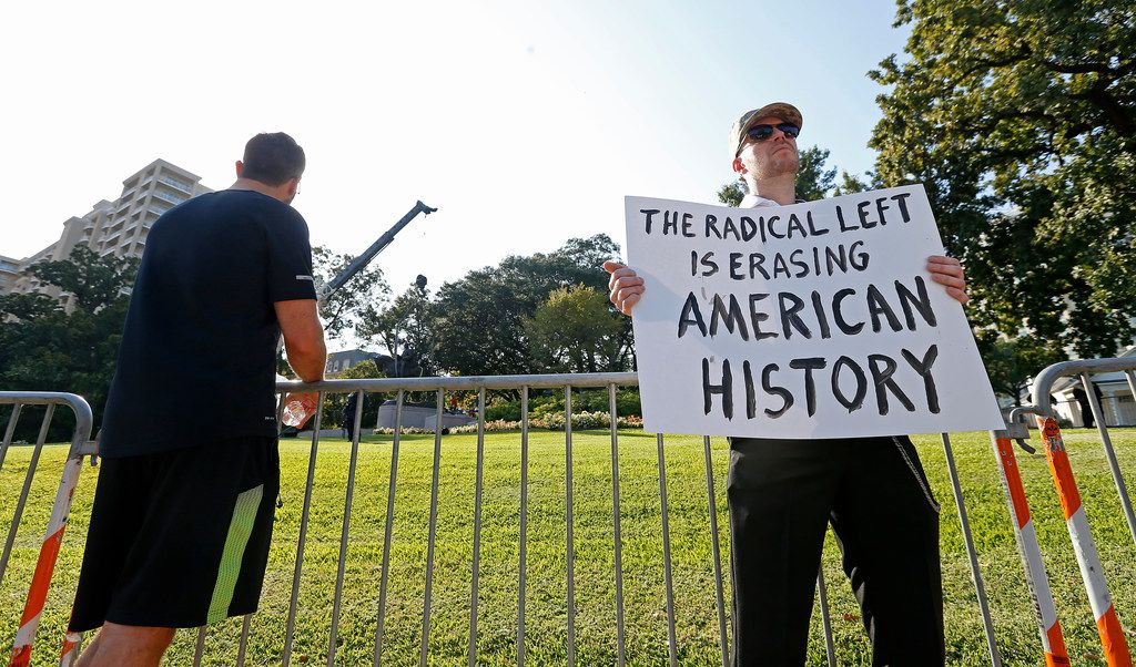 Frank Darbo (right) holds a sign as crew members work to remove the Robert E. Lee statue in the background at Robert E. Lee Park in Dallas on Sept. 14, 2017.
