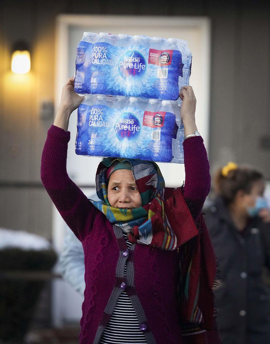 Una mujer carga un paquete con botellas de aguas en un centro de distribución en Literacy Achieves en Vickery Meadows el jueves 18 de febrero de 2021, en Dallas.