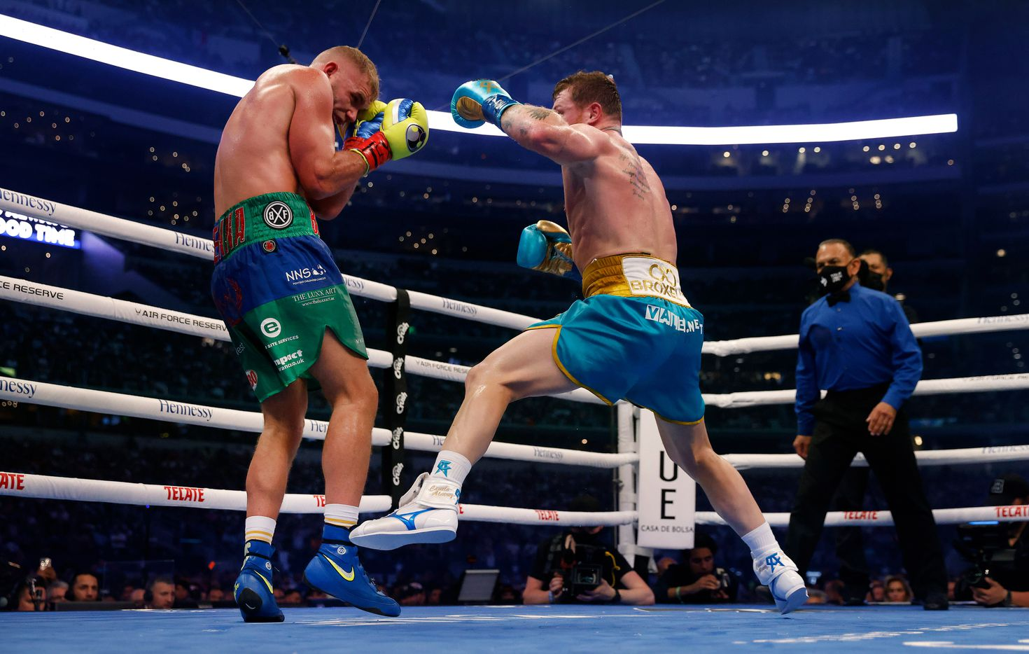 Boxer Canelo Alvarez (right) delivers a flurry of punches on Billy Joe Saunders during their super middleweight title fight at AT&T Stadium in Arlington, Saturday, May 8, 2021. Saunders couldn't go beyond the eighth round because he sustained an eye injury and could not see. (Tom Fox/The Dallas Morning News)