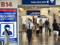 Pilots walk by signs in DFW International Airport's Terminal B directing travelers to stop the spread of COVID-19.