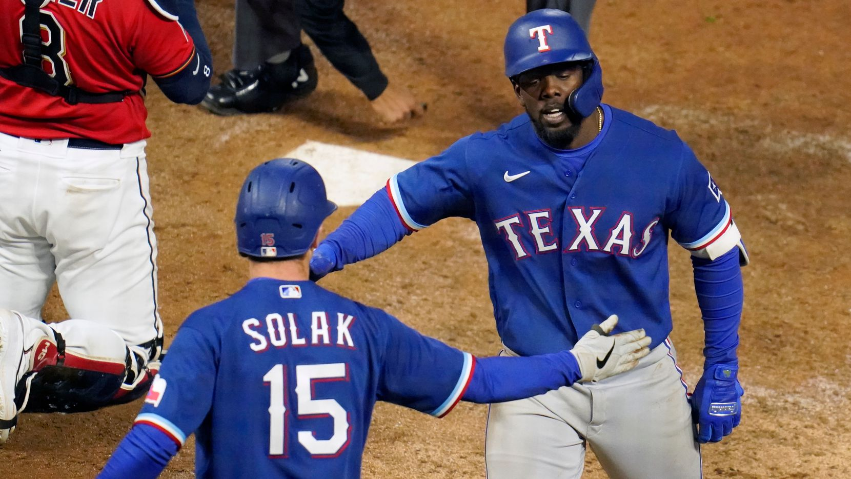 Texas Rangers' Adolis Garcia, right, is congratulated by Nick Solak after Garcia's two-run home run off Minnesota Twins pitcher Brandon Waddell in the tenth inning of a baseball game, Tuesday, May 4, 2021, in Minneapolis. The Rangers won 6-3. (AP Photo/Jim Mone)