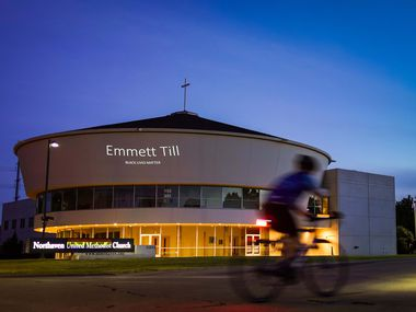 """A cyclist crosses Preston Road at a stoplight as the name of Emmett Till is projected on the front of Northaven United Methodist Church on Thursday, June 18, 2020, in Dallas. The church is projecting the names of people who have been killed by police or white violence along with messages such as """"Jesus Weeps,"""" """"Say Their Names"""" and """"Black Lives Matter."""""""