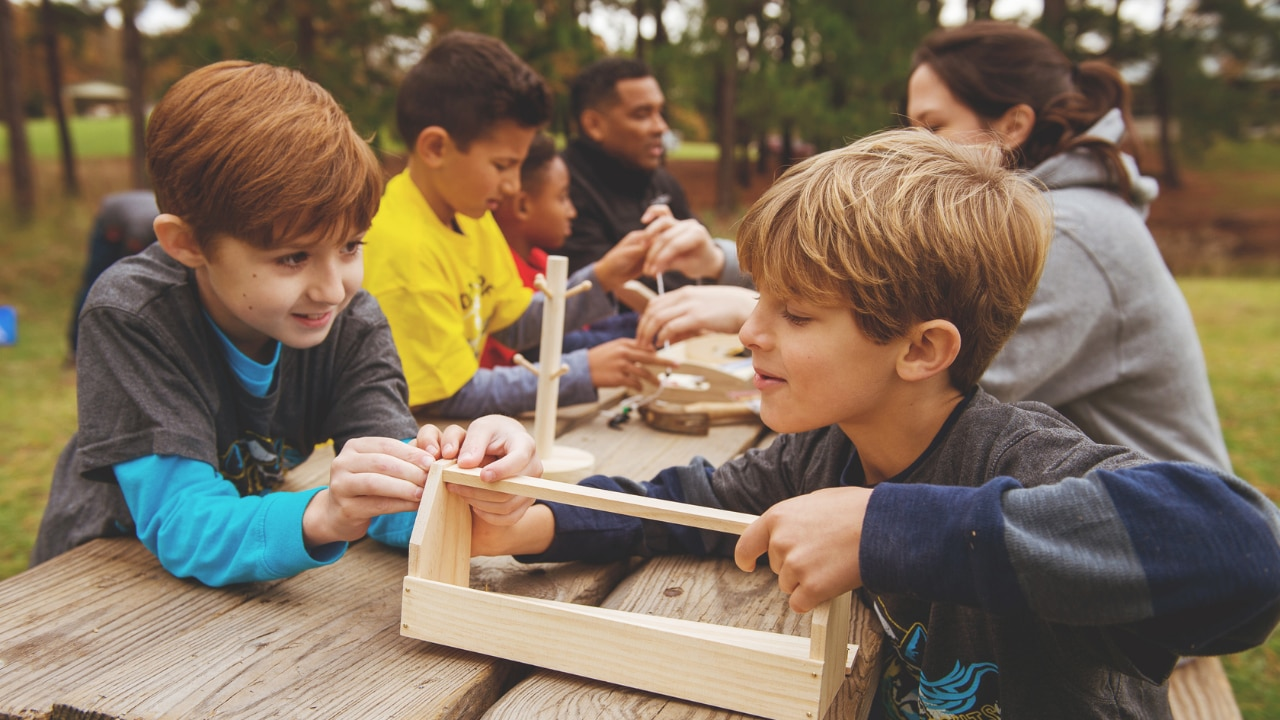 Two young boys work to assemble a wooden craft with their scouting group and chaperones.