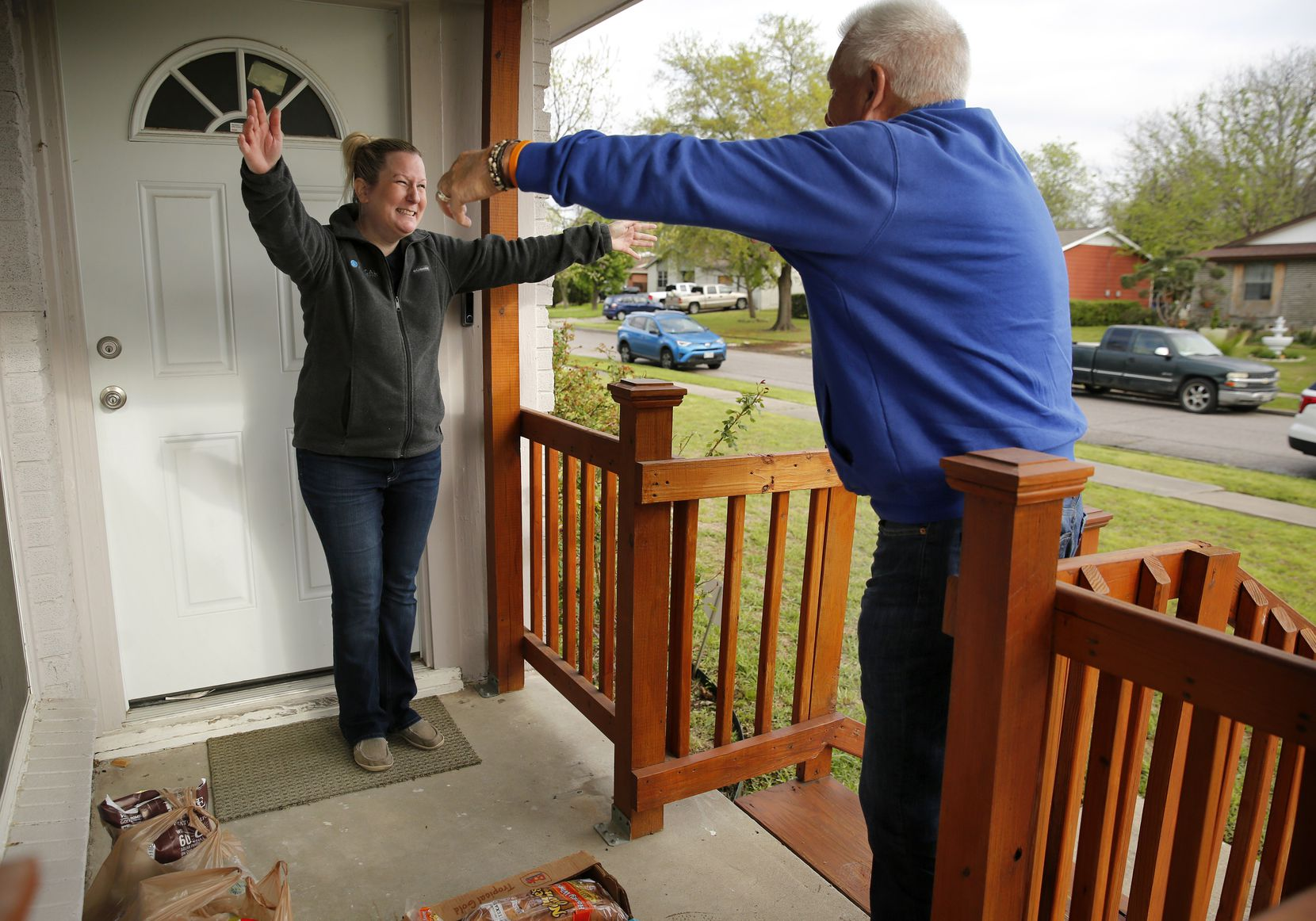 Eddy Clinton of Plano, a former coach and local sportscaster, gives Kristin Tarrence a socially distanced air hug while delivering a load of groceries to her Farmers Branch home.