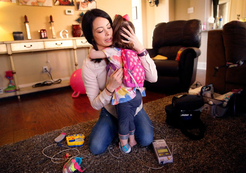 Natalie Gregory receives a hug from her 2 year-old daughter Christina who suffers from CCHS (Congenital Central Hypoventilation Syndrome), a genetic disorder that affects her breathing. The Gregory's have two pediatric nurses that work around the clock keeping a watchful eye on Christina at their Southlake,Texas home, Tuesday, January 31, 2017. Christina has to wear a diaphragmatic pace maker in a backpack that keeps her breathing on track as well as a ventilator unit that hooks up to a trachea tube in her neck. The Gregorys are affected by Texas' change to their Medicare healthcare coverage, switching to a MCO plan from an HMO plan, limiting their care to within the region -a cumbersome issue for families dealing with 24/7 care. (Tom Fox/The Dallas Morning News)