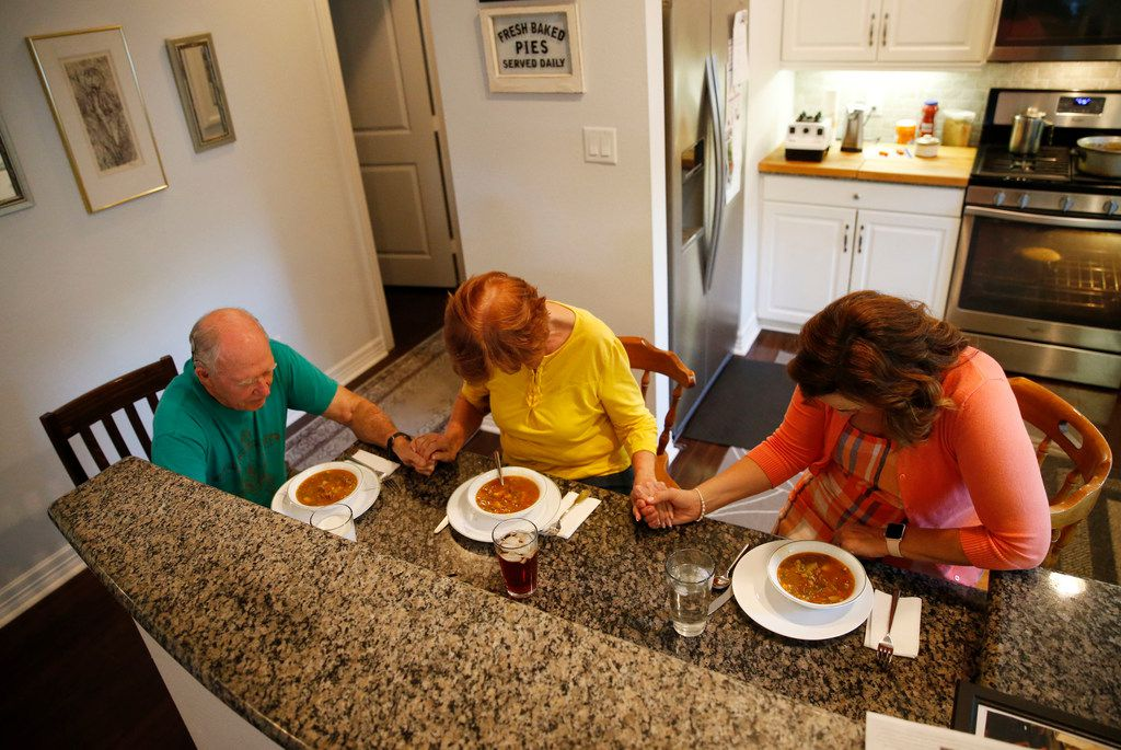 Henry Brigman, Iris Brigman and Amy Hardesty pray before dinner at the Brigman home in Frisco on Aug. 29.  Hardesty is renting a room at the Brigman home while teaching at Fisher Elementary School in Frisco.