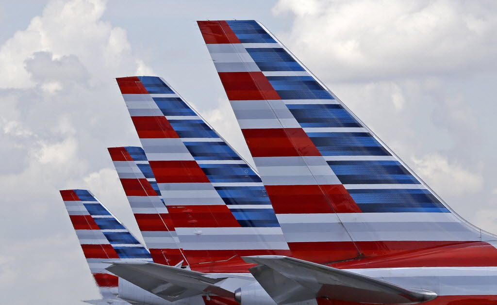 """FILE - This photo July 17, 2015, photo shows the tails of four American Airlines passenger planes parked at Miami International Airport, in Miami.  American Airlines, on Wednesday, Dec. 9, 2015, says it will start selling """"premium economy"""" service on international flights, with leather seats, entertainment systems and meals. The seats will cost more than coach but less than business class, although American isn't stating prices. (AP Photo/Alan Diaz, File)"""