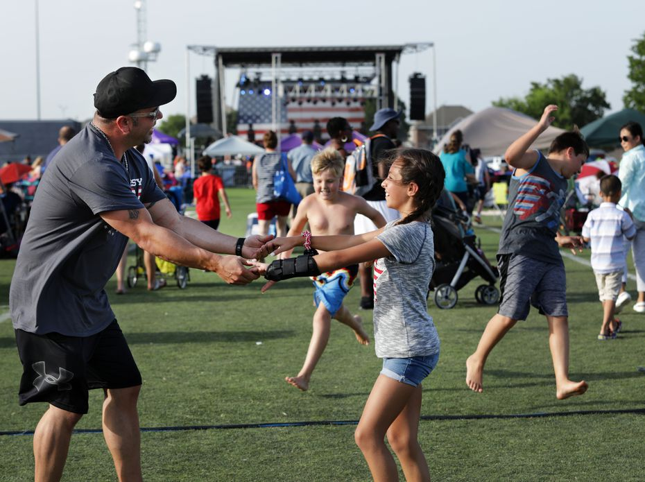 Ted Paulmeno and 11-year-old Adriana Paulmeno dance to music during the Allen USA Celebration at Celebration Park on June 30, 2018.