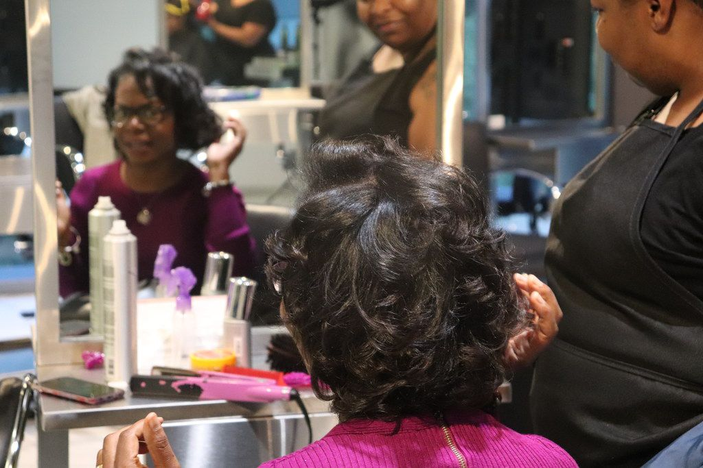 A woman looks at her reflection after getting her hair blown out by a Pressed Roots stylist.
