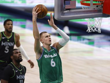 Dallas Mavericks forward Kristaps Porzingis (6) goes up for a dunk as Minnesota Timberwolves center Naz Reid (11) trails during the first quarter of play at American Airlines Center on Monday, February 8, 2021 in Dallas.