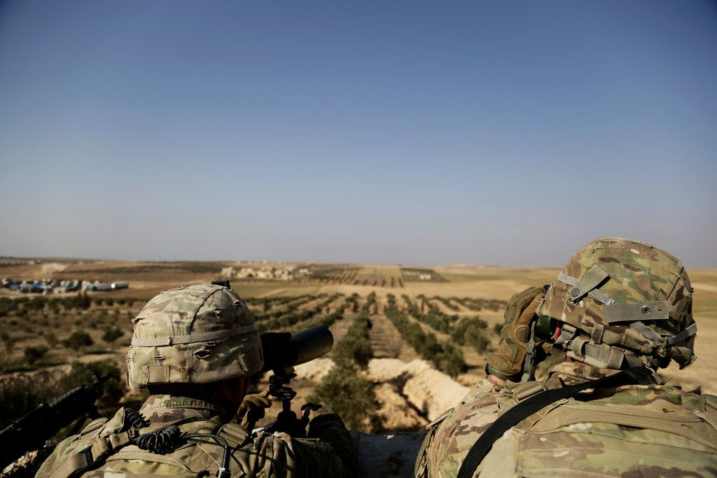 In this Feb. 7, 2018 file photo, American troops look out toward the border with Turkey from a small outpost near the town of Manbij, northern Syria.