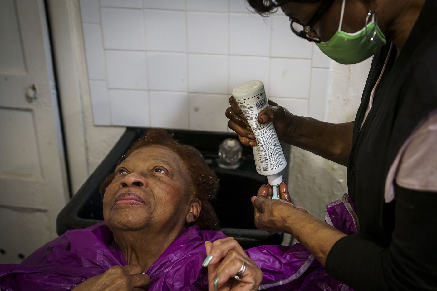 Earnestine Tarrant washes the hair of client Vera Harris at her hair salon. After four decades in business, she decided to close on New Year's Eve.