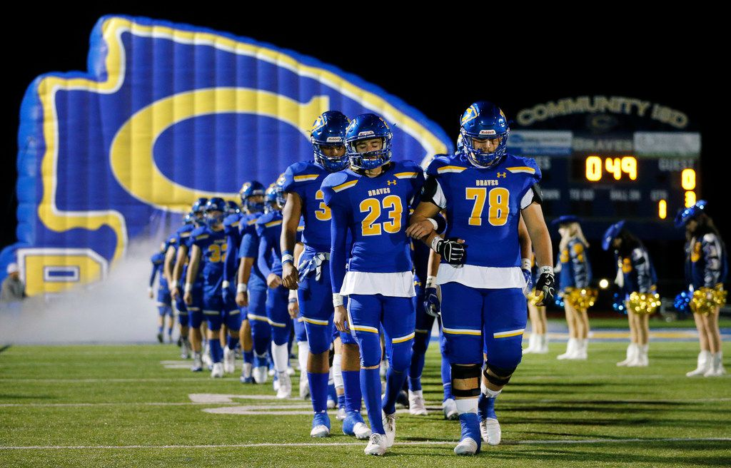 Community High football players, including Tanner Phillips (23) and Noe Rodriguez (78), silently walk arm-in-arm as they were introduced before their football with Dallas Roosevelt at Community ISD Stadium in Nevada, Texas, Friday, November 8, 2019. They were playing with heavy hearts after four of their classmates were killed in a tragic vehicle accident earlier this week. (Tom Fox/The Dallas Morning News)