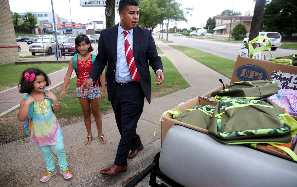 Teacher Adan Gonzalez helps Lluvia Rivera, 5, and her sister, Allison Rivera, 10, pick out mochilas, backpacks for school. Gonzalez attended Bowie, grew up poor, and purchased the backpacks himself.