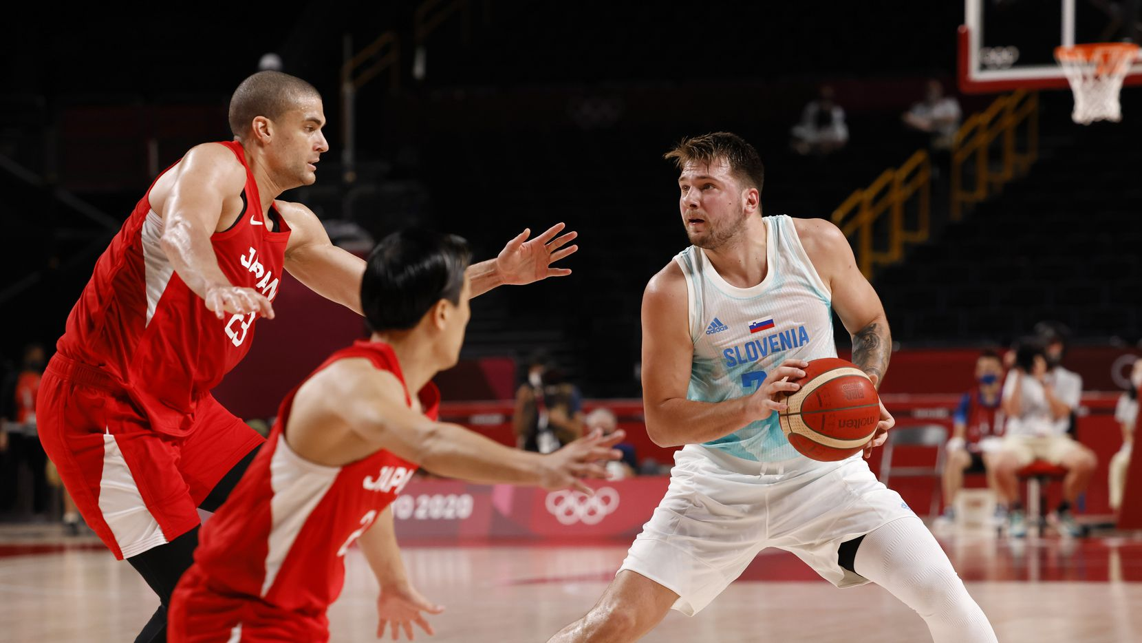 Luka Doncic (der) de Eslovenia da un paso atrás para un intento de tres puntos mientras el japonés Gavin Earl Edwards  defiende en un juego de baloncesto en los Juegos Olímpicos de Tokio, el 29 de julio de 2021. (Vernon Bryant / The Dallas Morning News)