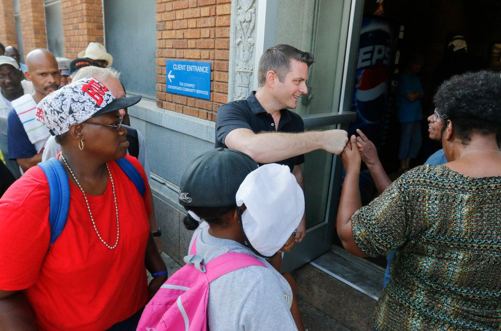 Jonathan Palant (center), founder and director of the Dallas Street Choir, greets members as they enter The Stewpot in downtown Dallas for the choir's weekly rehearsal. Choir members line up at The Stewpot as early at 8:30 a.m. to make it into rehearsal.