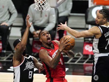 Houston Rockets forward Sterling Brown, center, shoots as Los Angeles Clippers forward Marcus Morris Sr., left, and guard Amir Coffey defend during the first half of an NBA basketball game Friday, April 9, 2021, in Los Angeles.