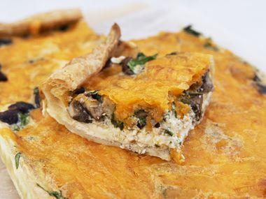 Una porción de quiche con queso espinacas y shiitake.