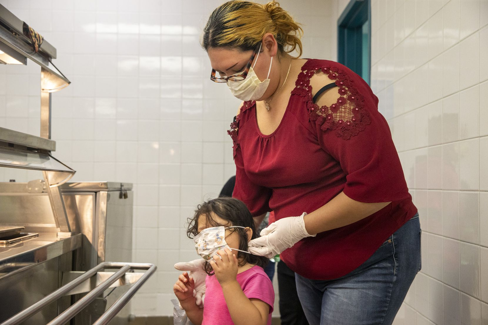 Angie Andrade readjusted her 3-year-old daughter Abigail's face mask while they picked up free sack lunches at J.T. Saldivar Elementary School in Dallas<EP> during spring break in March.
