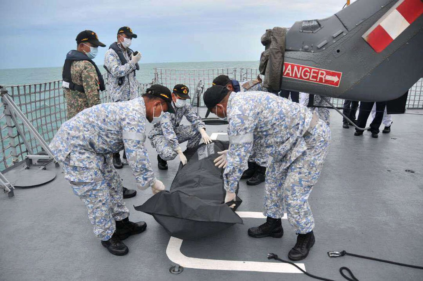 Malaysian navy sailors cover an unidentified body after it was found in the water off the coast of Malaysia on Tuesday.
