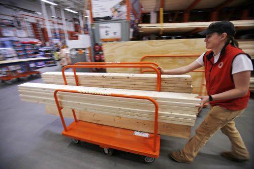 Una clienta empuja una plataforma móvil con madera en Home Depot (AP /Gene J. Puskar)