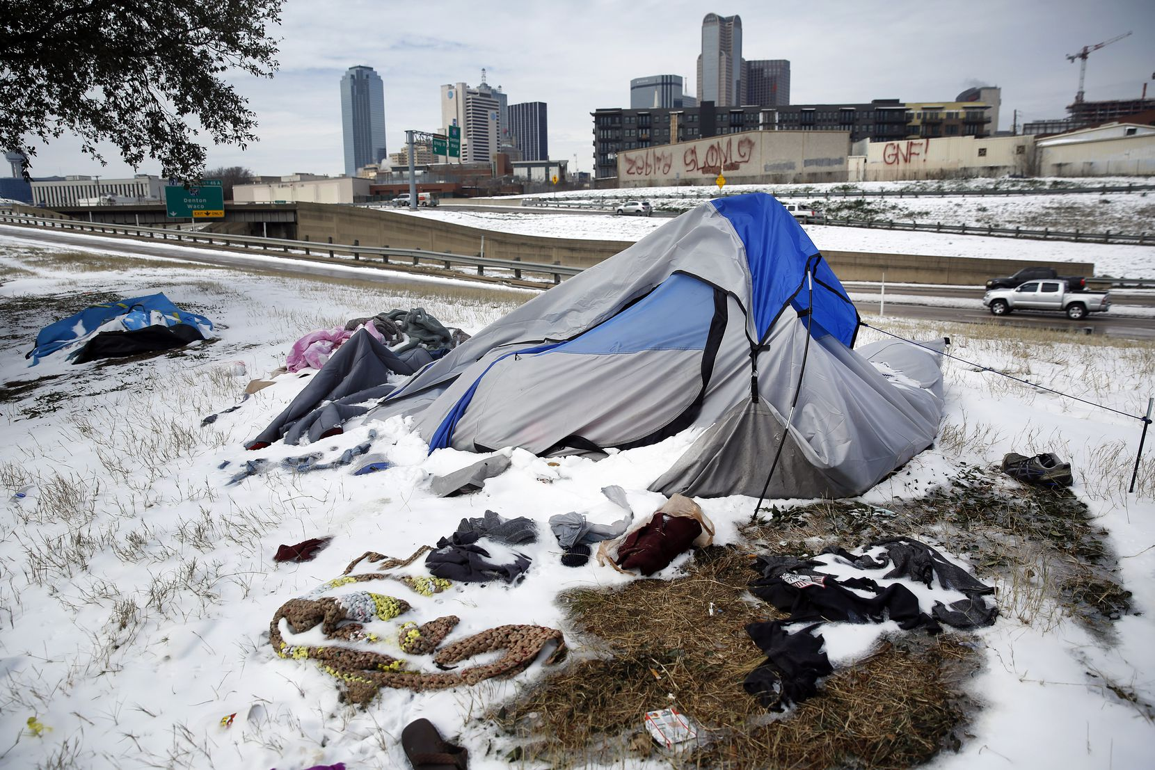 Snow-covered tents pitched along Interstate 30 were abandoned by their owners as a snow storm and sub-freezing temperatures rolled into downtown Dallas. A nearby warming shelter at the Kay Bailey Hutchison Convention Center was set up by OurCalling and was housing about 700 people who found refuge from the deadly cold temperatures in Hall E-F.  (Tom Fox/The Dallas Morning News)