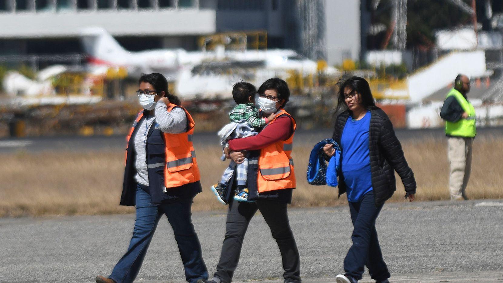 Agentes de migración de Guatemala con mascarillas protectoras recibieron en el Aeropuerto Internacional de Guatemala a un grupo de migrantes que fueron deportados desde Estados Unidos.