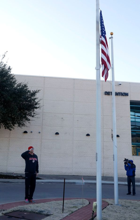 Former Marine Bill DeButy of Richardson placed flowers and saluted at the flagpole in front of the Richardson, Texas police headquarters on Thursday, Feb. 8, 2018. A Richardson police officer was fatally shot the night before at an apartment complex