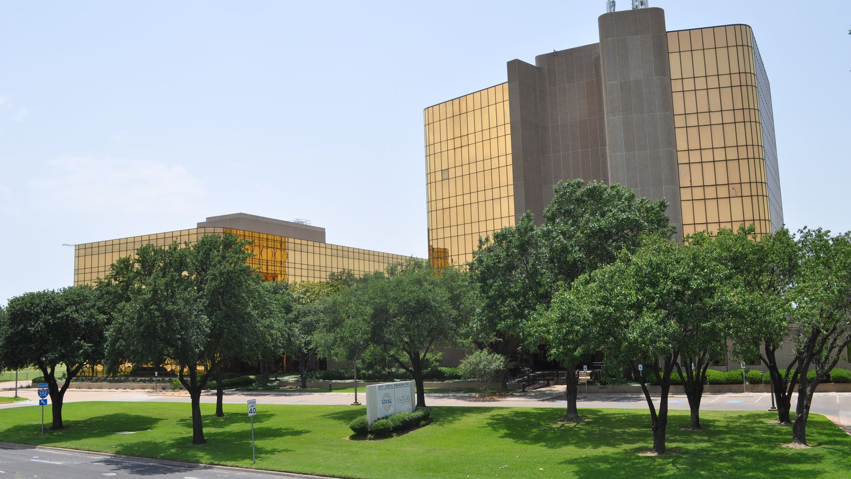 The gold glass Stemmons Freeway buildings were purchased by Dallas-based Ricchi Group.