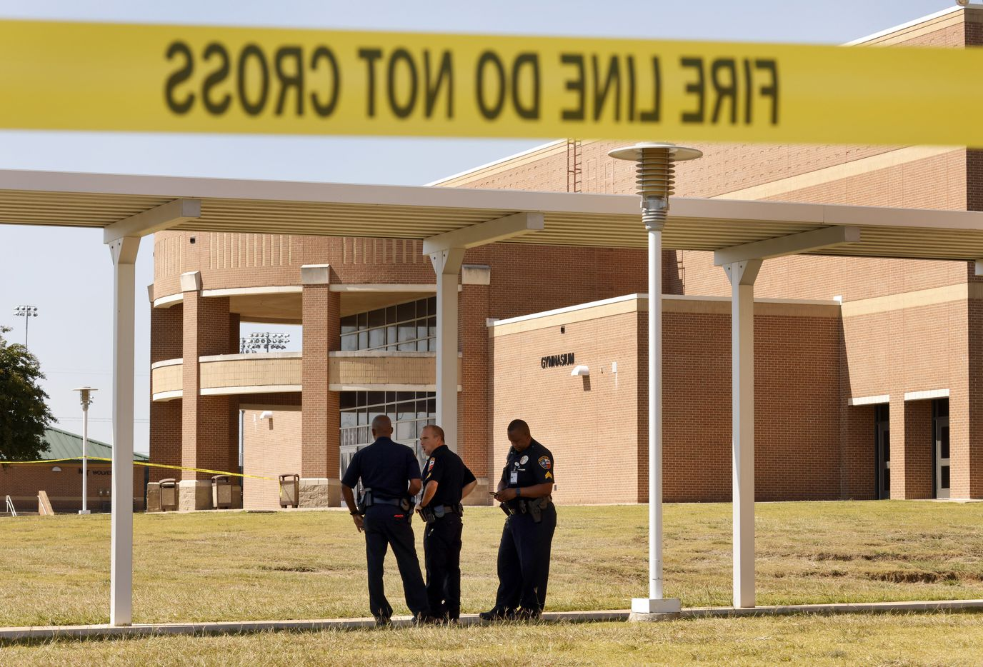 Mansfield ISD police officers secure the door where most of the activity took place following a shooting inside Mansfield Timberview High School in Arlington, Texas, Wednesday, October 6, 2021. Four people were injured in the shooting and the suspect turned himself into the Arlington police. (Tom Fox/The Dallas Morning News)