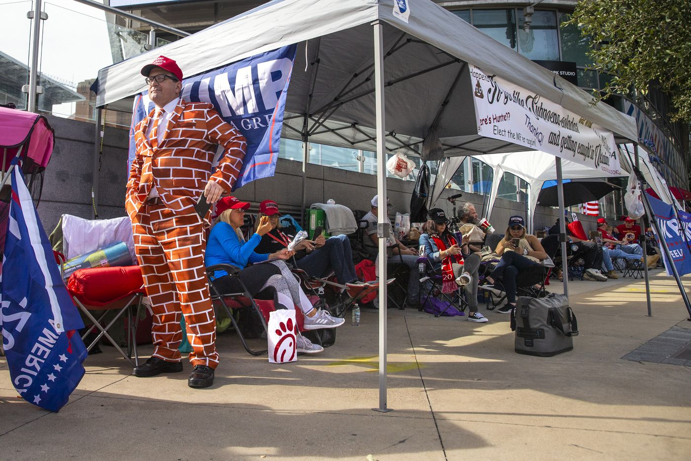 Blake Marnell wears a brick suit while camping out in line in front of the American Airlines Center in Dallas on Wednesday, Oct. 16, 2019. President Donald Trump will host a rally at the center on Thursday evening.