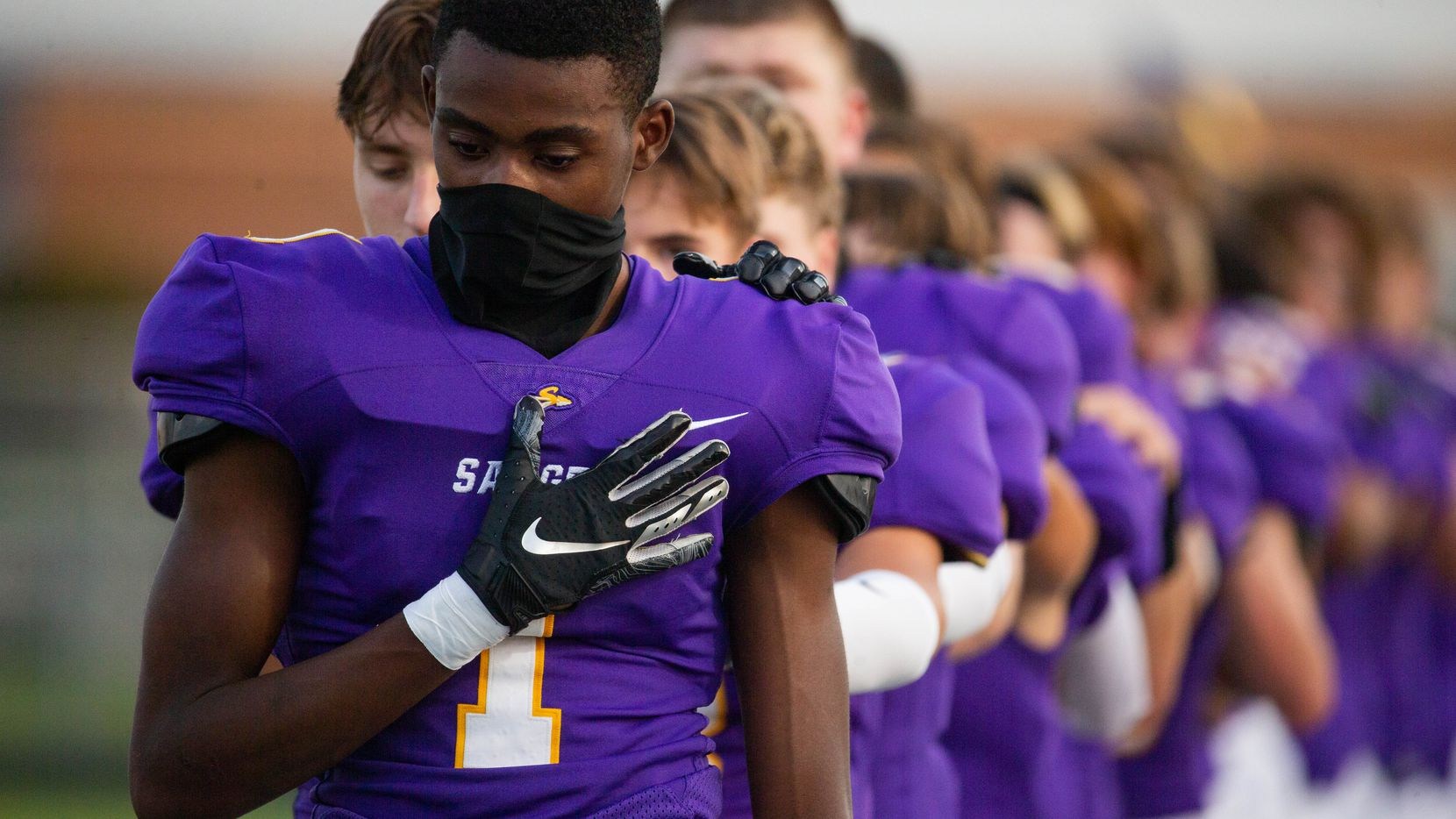 Sanger's Josh Henry wears a neck gaiter during the national anthem before the start of a game against Lake Worth High School on Sept. 4, 2020 in Sanger.