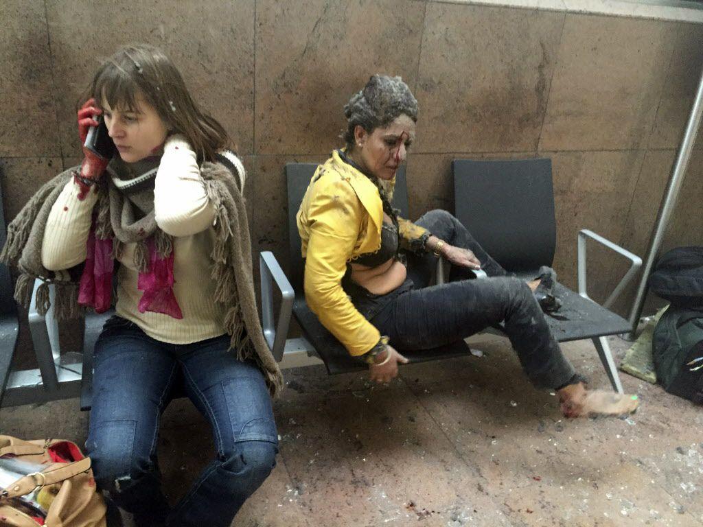 Dos mujeres heridas a la espera de ayuda en  el aeropuerto de Bruselas donde ocurrieron las explosiones./Ralph Usbeck via AP)