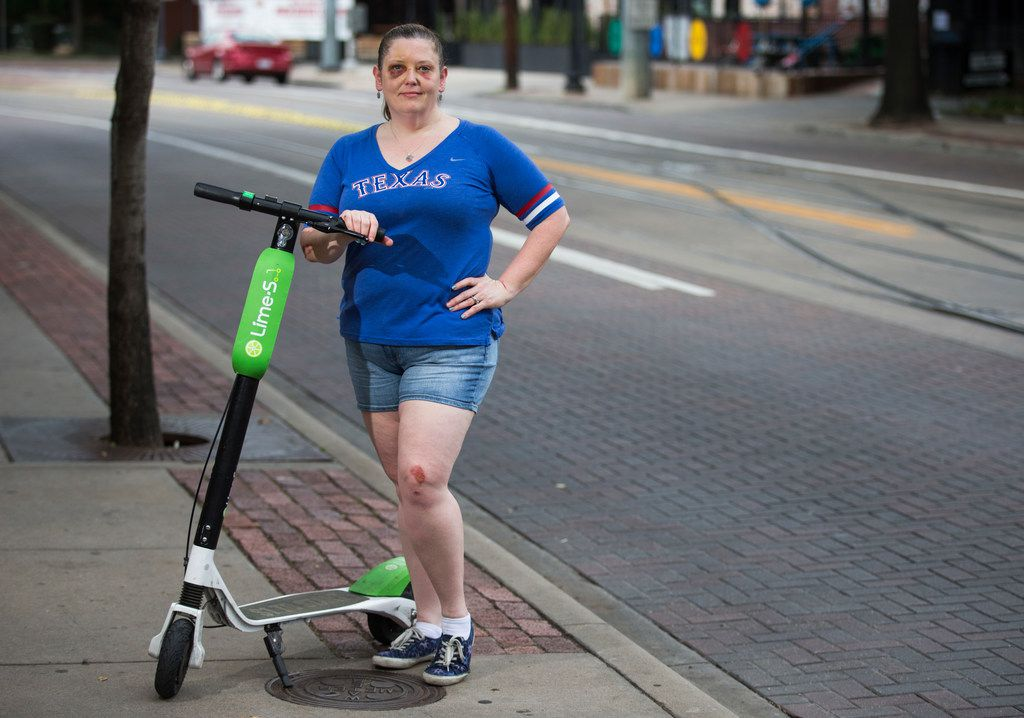 Kelley Mitchum posed for a photo with a Lime scooter near Christies Sports Bar on McKinney Avenue in Dallas on Thursday. Mitchum was injured when she fell off of a Lime scooter while she crossed over some trolley tracks a few feet from where she stood for the photo. She was not wearing a helmet.