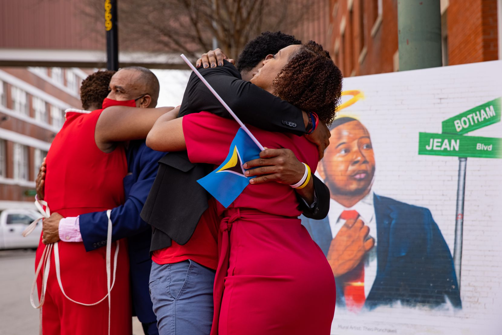 Botham Jean's family immediately embraced after the street sign bearing his name was unveiled, to cheers, on Saturday.