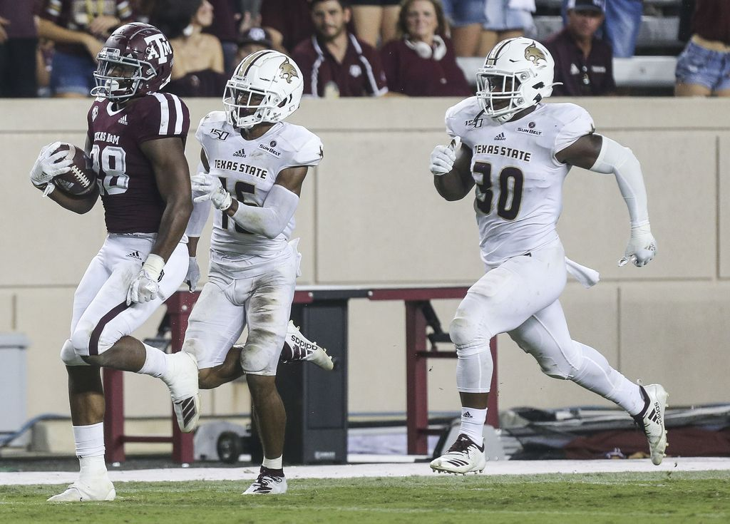 Texas A&M Aggies running back Isaiah Spiller (28) breaks away from Texas State Bobcats cornerback JaShon Waddy (16) and linebacker Nikolas Daniels (30) during the third  quarter of a college football game between Texas A&M and Texas State on Thursday, Aug. 29, 2019 at Kyle Field in College Station, Texas.