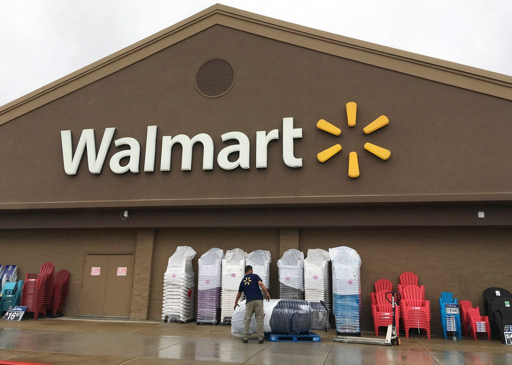 A worker stacks merchandise outside a Walmart in Salem, N.H. Walmart is boosting its starting salary for U.S. workers to $11 an hour, giving a one-time $1,000 cash bonus to eligible employees and expanding its maternity and parental leave benefits. The retailer said Jan. 11, 2018, that changes to its compensation and benefits policy will impact more than a million hourly workers in the U.S., with the wage increase effective next month.